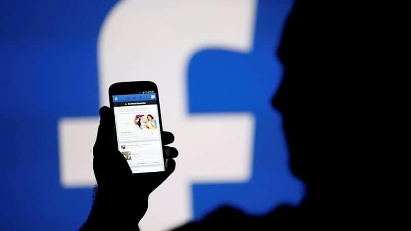 pessoa usando o Facebook de seu celular