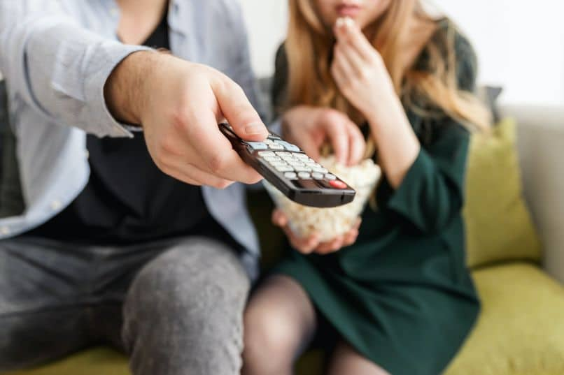 casal assistindo tv com controle remoto