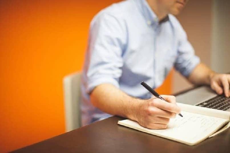 homem escrevendo no caderno no escritório