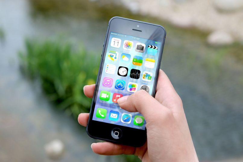 iphone na mão com menu de apps