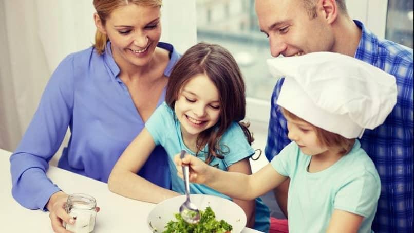 família feliz junta preparando comida saudável