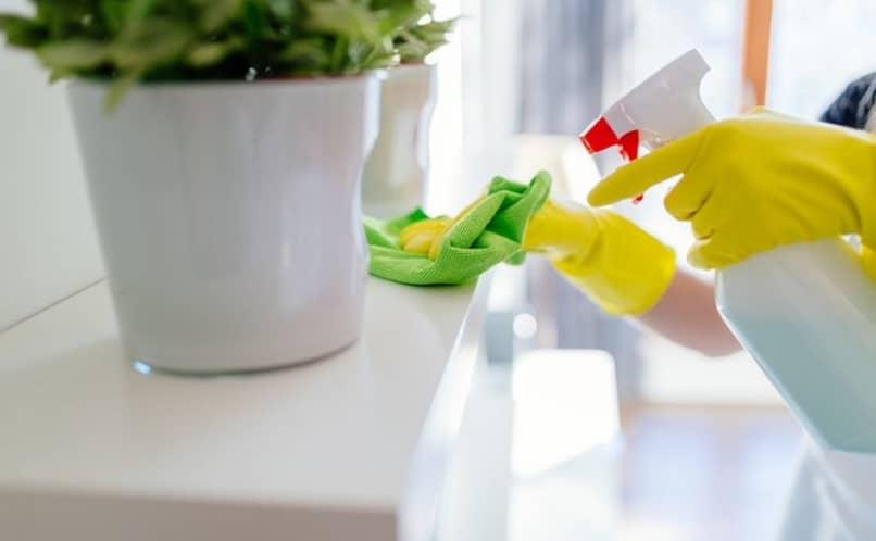 pessoa limpando prateleira com pano