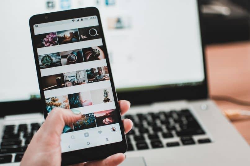 instagram no smartphone com laptop e mão