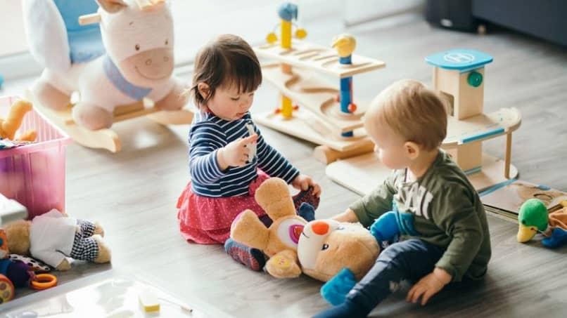 bebês brincando com um urso no berçário