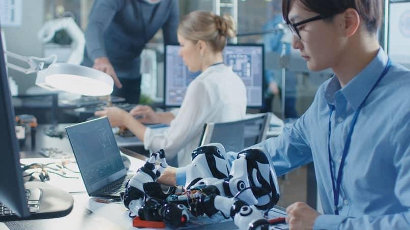 pessoas montam robótica de trabalho de robô