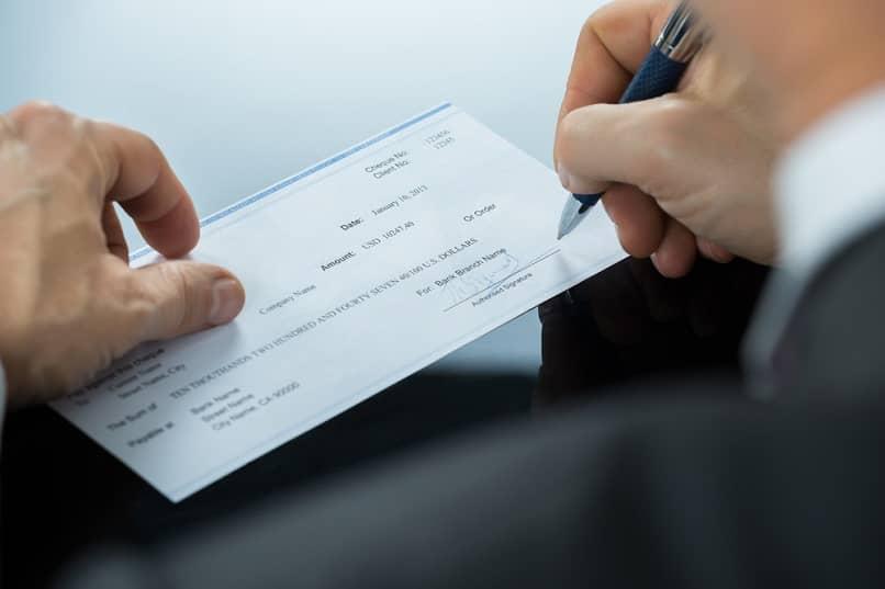 pessoa preenchendo cheque sinal de pagamento