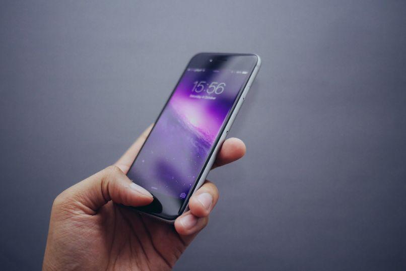iphone na mão em fundo cinza