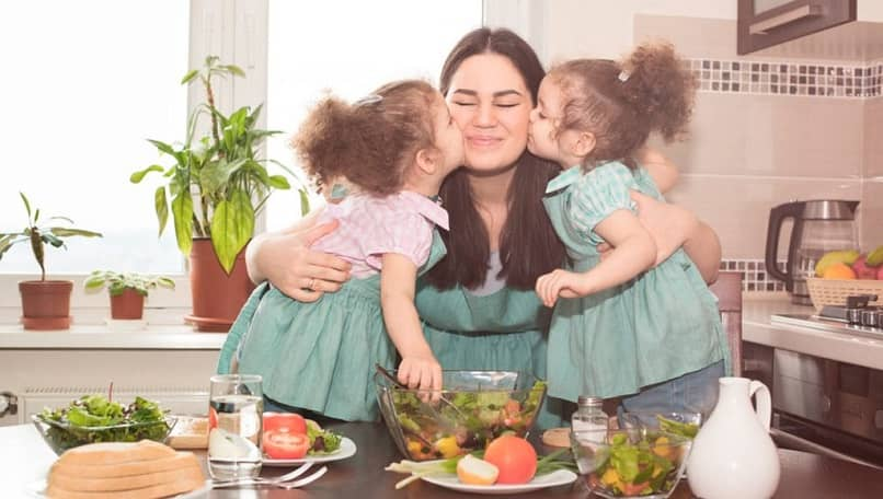 mãe abraçando suas duas filhas