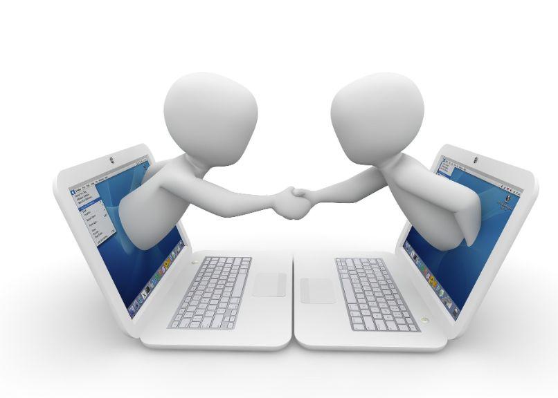 pessoas apertando as mãos em laptops