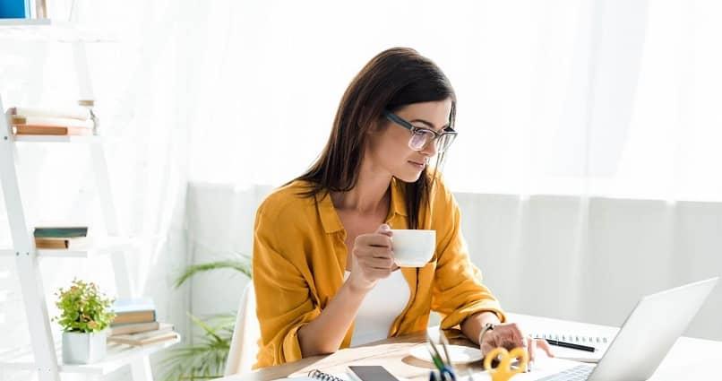 mulher bebida xícara café trabalho laptop escritório