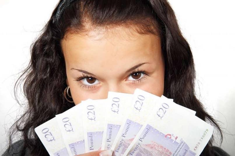 adolescente com um leque de dinheiro no rosto