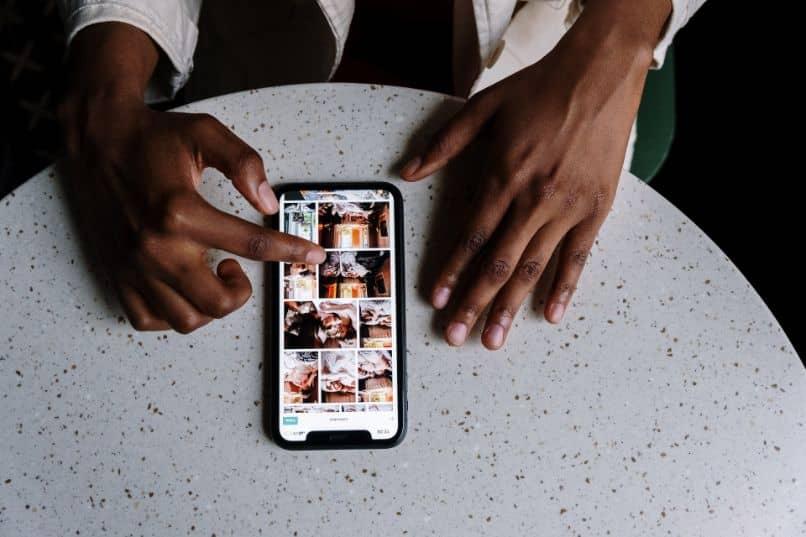 smartphone com instagram e mãos na mesa